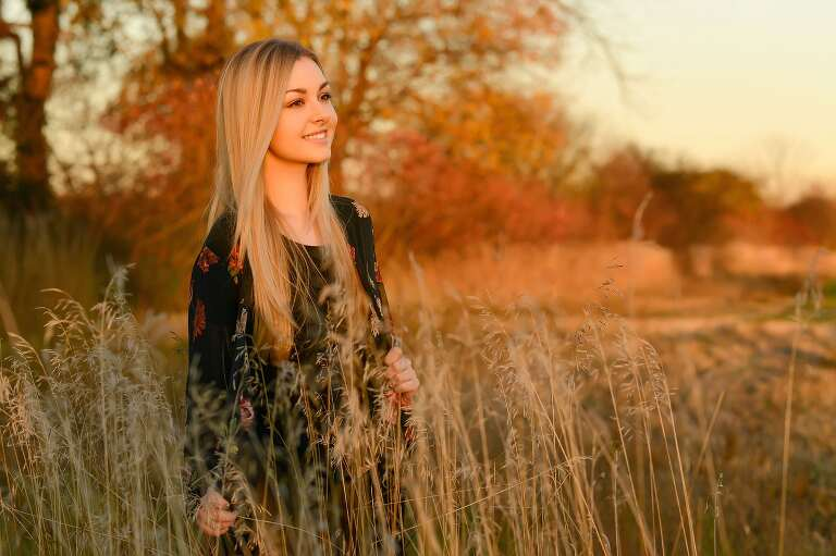 A high school senior poses in a field with golden light surrounding her